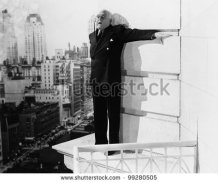 stock-photo-man-standing-on-the-ledge-of-a-building-and-looking-feared-99280505