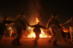 """Bulgarians carry bells on their waists as they dance around a bonfire during their """"Kukeri"""" ritual in the town of Batanovtsi, some 35 km ( 22 miles) south from the capital Sofia, on late Monday, Jan. 13, 2014. """"Kukeri"""" is a pagan Bulgarian masked ritual of Thracian origins, performed between Christmas and Lent by costumed men in sheepskin garments, bells and masks, who walk around and dance to scare away the evil spirits, in hope to provide a good harvest, health, fertility, and happiness. (AP Photo/Valentina Petrova) ORG XMIT: VP107"""
