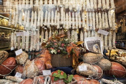 BOLOGNA, ITALY - 6 APRIL, 2014: Salamis, hams and sausages are exposed in the shop window of Tamburini, a deli in the historical centre of Bologna, Italy, on April 6th 2014